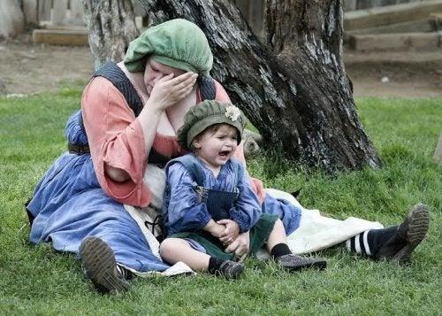 Grædende baby sidder for fødderne af sin mor, der lider af udbrændthed