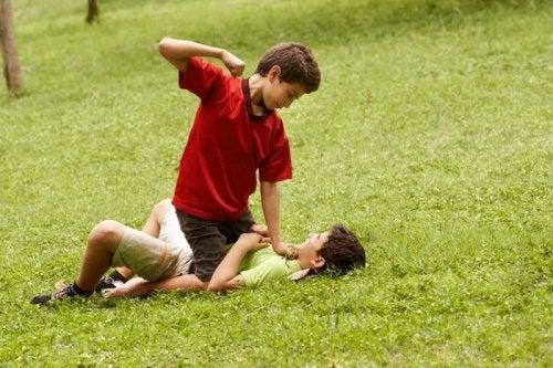2 børn slår hinanden på en græsplæne