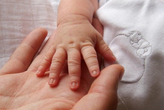 mor og baby holder hånd