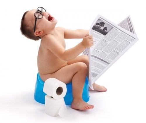 dreng læser avis på potten