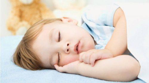 Et sovende barn i sengen. Hvorfor spørger børn om vand