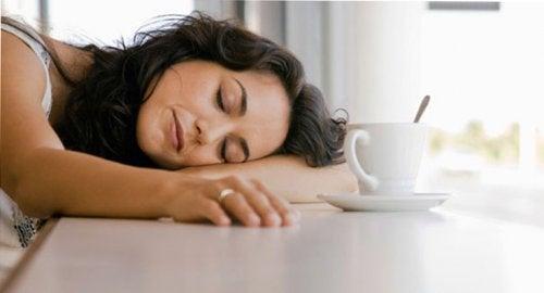 udmattet kvinde sover på bordet