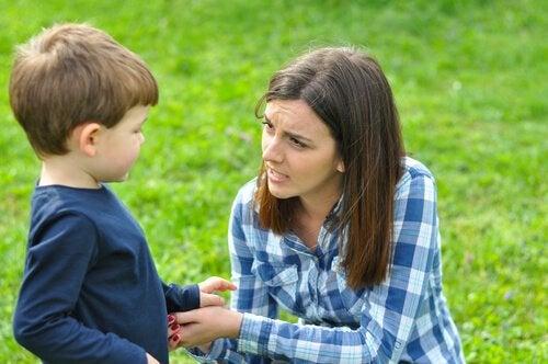 mor snakker med sit barn i en park