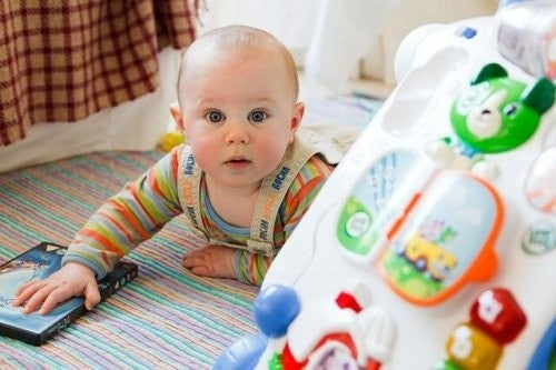 baby leger og kigger på kameraet