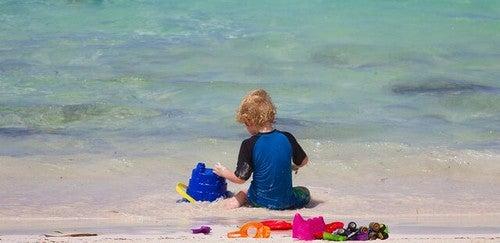 barn sidder og leger på en strand