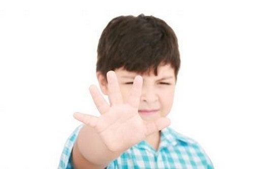 dreng rækker hånden ud og siger stop