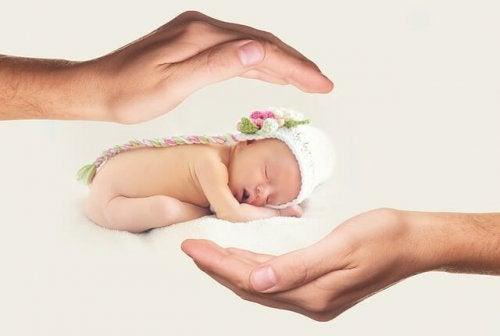 Forældre holder nyfødt baby i en hat