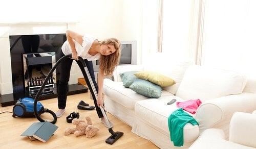 kvinde støvsuger og rydder op i hjemmet