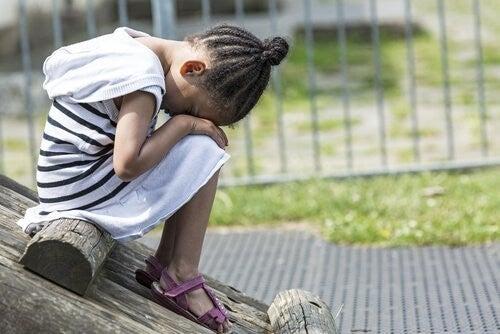 pige sidder på legeplads og er ked af det