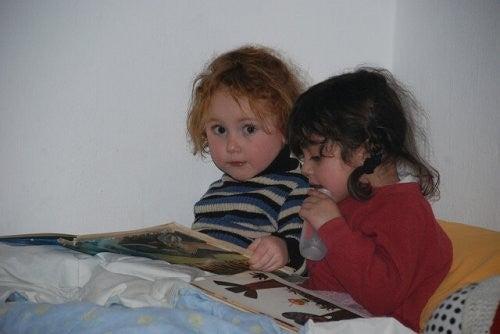 børn læser godnathistorie i sengen, inden de skal sove