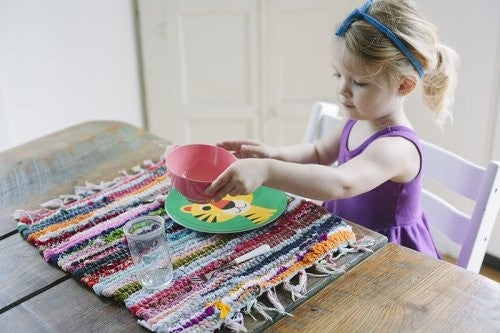 pige sidder ved bordet med skål, tallerken og glas