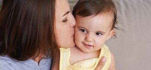 baby får kys af sin mor