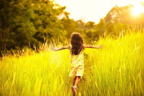 Lille pige løber gennem en eng