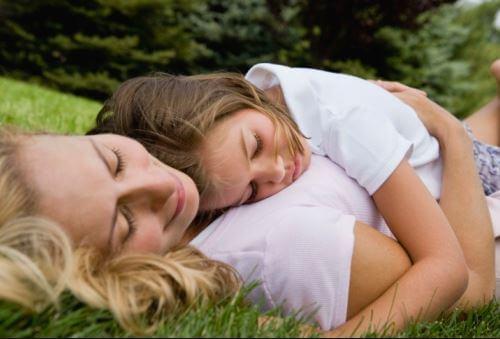 Mor ligger på græsset med datter