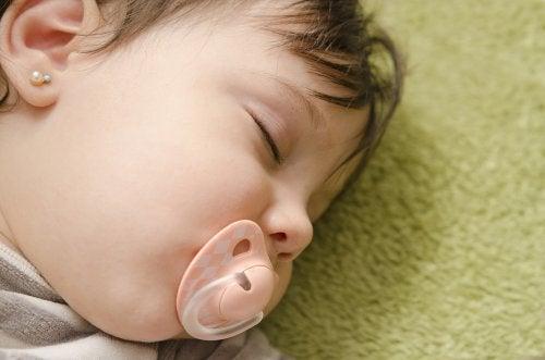 baby med ørering sover. Øreringe for børn.