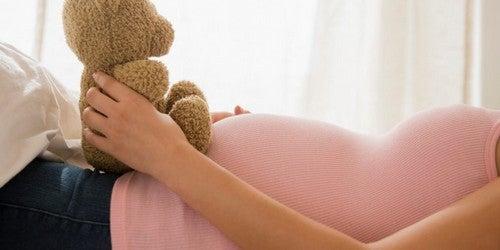 gravid kvinde holder en bamse