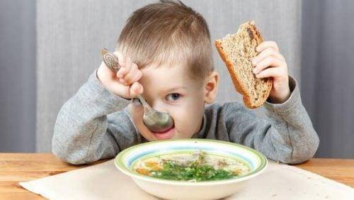 Barn spiser suppe med brød
