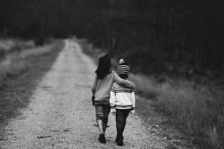 Pige går med hånd om lille dreng