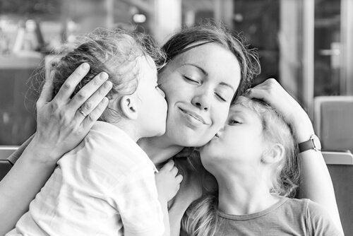 Mor bliver kysset af sine børn