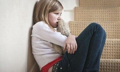 Pige sidder på trappen og er ked af det