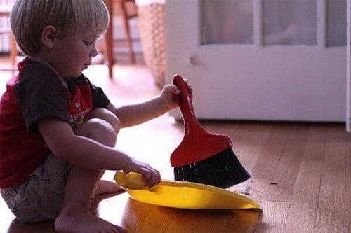 Dreng hjælper til ved at feje gulvet