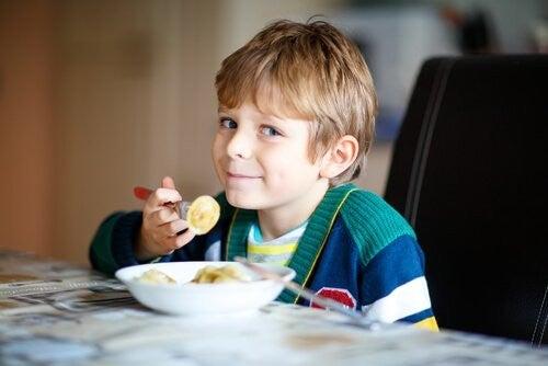 Dreng spiser snack ved køkkenbord
