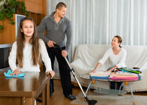 Datter hjælper mor og far med rengøringen i hjemmet