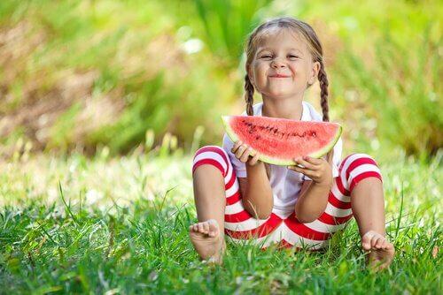 Glad pige spiser vandmelon