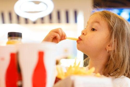 Pige spiser en pomfrit