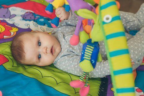 Baby udfører stimulerende øvelser med legetøj