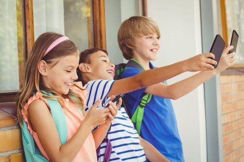 Smilende børn med telefoner frygter ikke teknologiske sygdomme hos børn
