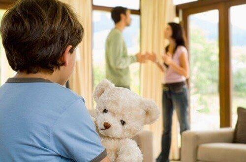 Forældre diskuterer foran dreng med bamse