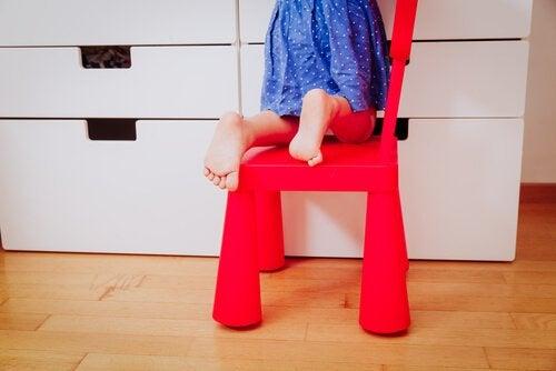lille barn der kravler på stol