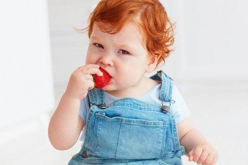 lille barn der spiser et jordbær
