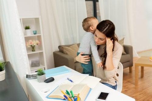 Mor med dreng på armen laver lektier