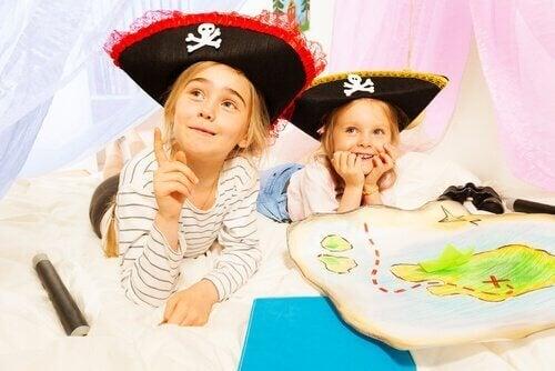 Piger klædt ud som pirater lege skattejagt som eksempel på udviklingsaktiviteter for børnehavebørn