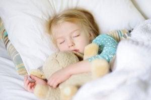 et barn sover trygt med sin bamse