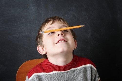 Barn balancerer blyant på næsen