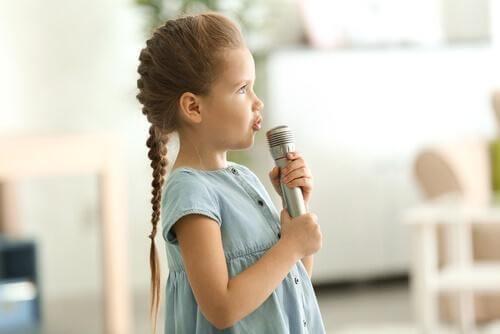 Pige synger ind i en mikrofon