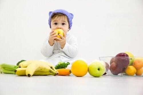 Baby omringet af forskellige frugter