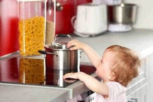 Barn rører ved varmt komfur