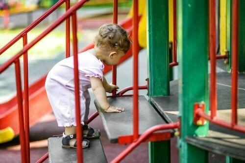 Baby kravler op ad trapper på legepladsen