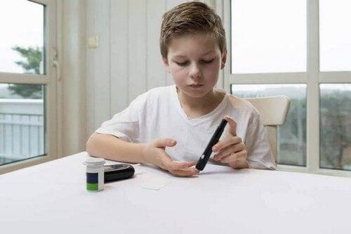 Dreng med diabetes måler sit blodsukker
