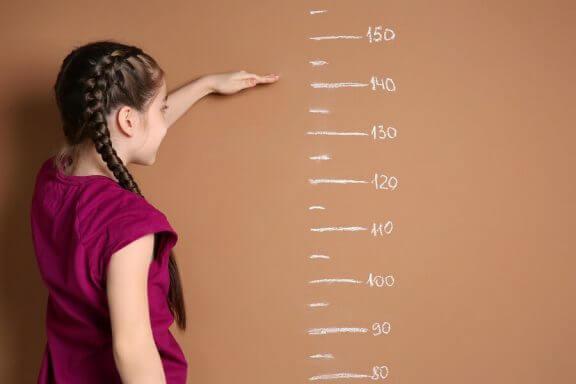 pige der kigger på en højdekurve på væggen