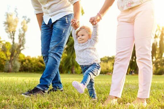 barn der går med sine forældre i hånden