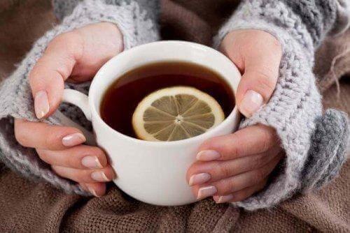 En varm kop te med en skive citron