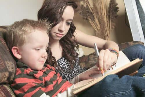 barnepige der hjælper dreng med at skrive