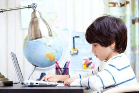 lille dreng der studerer på computer