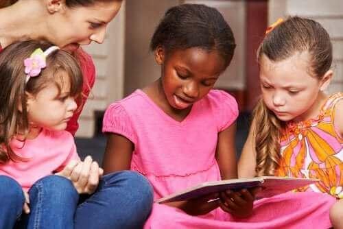 små piger der læser med voksen