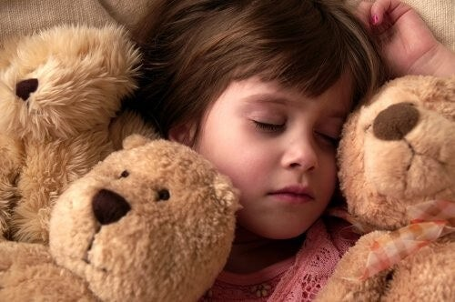 Pige sover blandt alle sine bamser